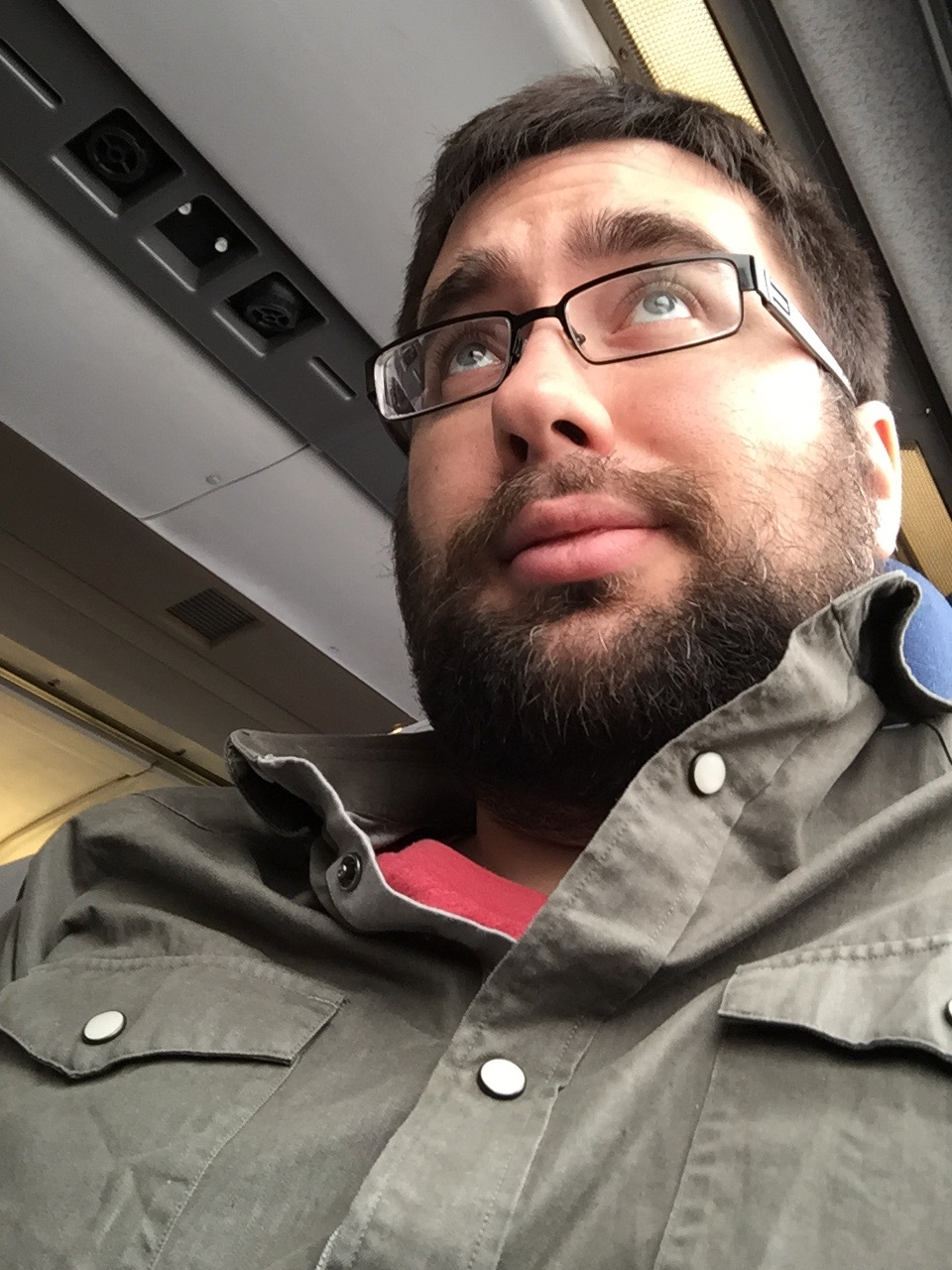 A selfie taken on a train, with odd composition that should look bad and yet somehow works, here.